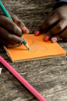 オレンジ色のポストイット紙にハートの形を描いて着色する女の子
