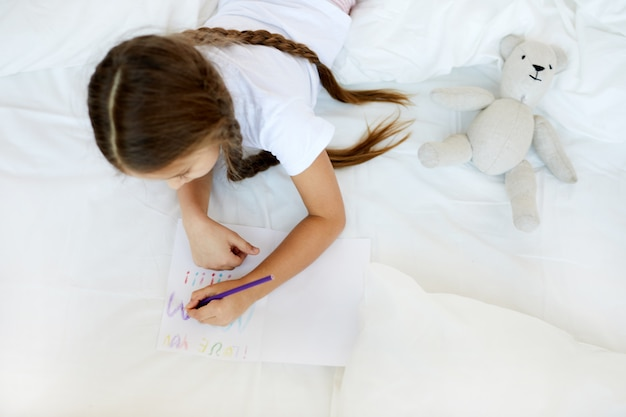 Girl drawing in bed