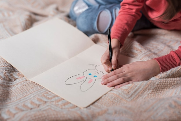 Girl drawing bunny on paper
