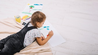 Girl drawing by water colors on paper and lying on floor