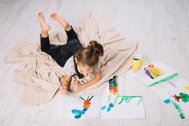 Girl drawing by water colors on paper near draws and lying on floor