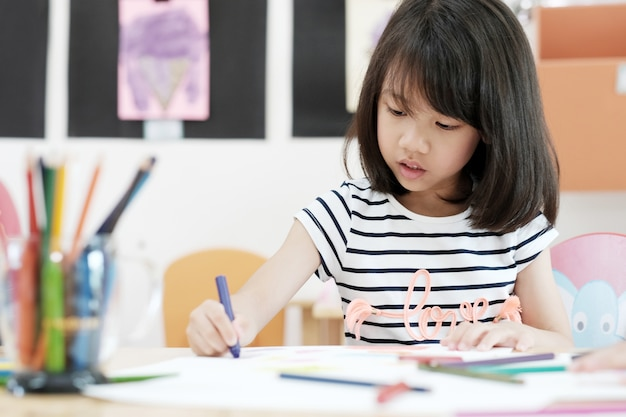 幼稚園の教室で色鉛筆を描く女の子