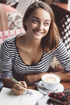 Girl drawing a cup of coffee in the notebook