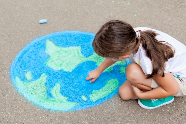 Girl drawing a globe earth with chalk on the asphalt