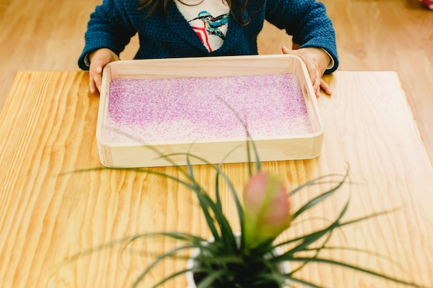 Girl drawing a heart on a tray with colored sand.