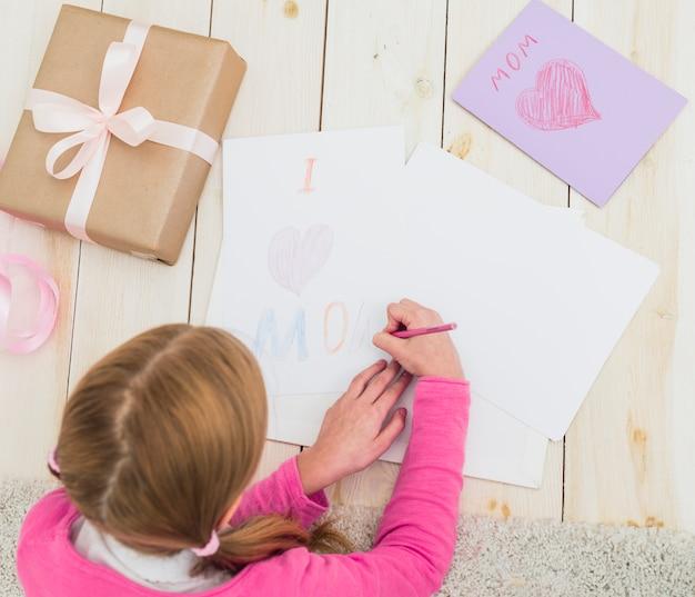 Девушка рисует, я люблю маму на листе бумаги
