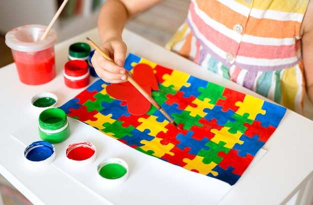 Girl drawing a multi-colored puzzles