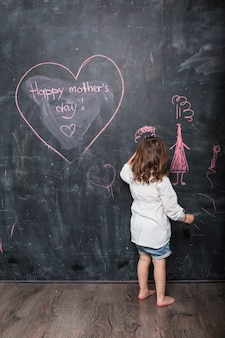 Girl drawing near happy mothers day inscription