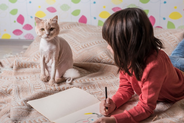 Girl drawing on paper looking at cat