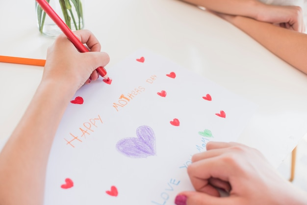 Girl drawing red hearts on paper with happy mothers day inscription