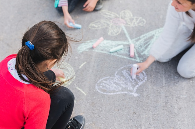 Girl drawing with chalk on road