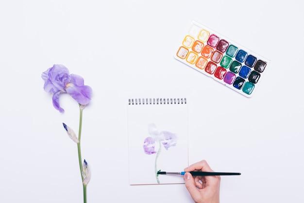 Девушка рисует синий цветок в тетради с акварелью