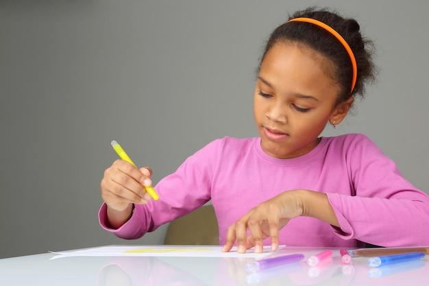 소녀는 흰 종이에 노란색 연필을 그립니다.