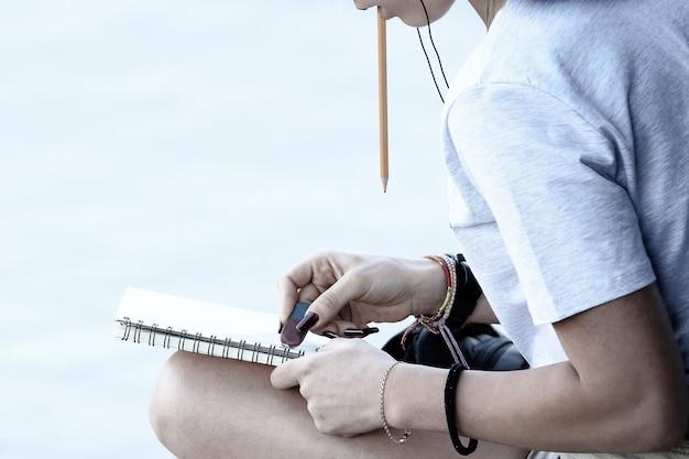 소녀는 포장 도로에 앉아 노트북을 그립니다. 예술 창의성과 아이디어
