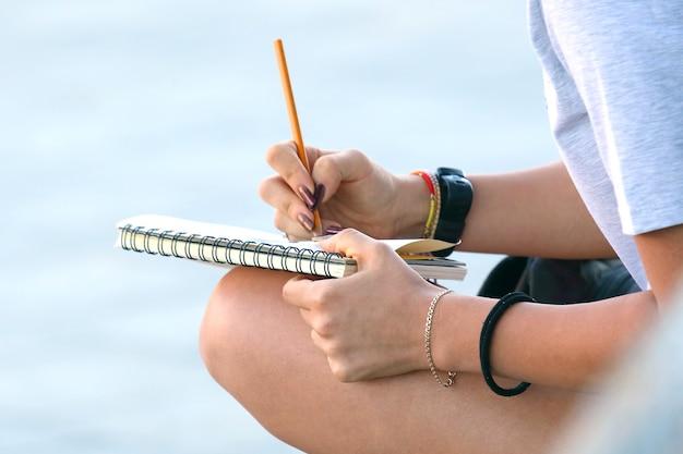 소녀는 포장 도로에 앉아 노트북을 그립니다. 창의성과 창의적 사고의 아이디어