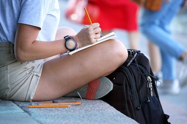 女の子は歩道に座ってノートを描きます