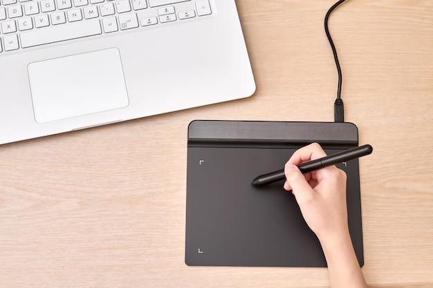 소녀는 펜으로 그래픽 태블릿에 그립니다.