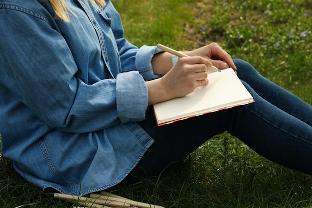 소녀는 푸른 잔디에 앉아 야외를 그립니다. 창의성 개념