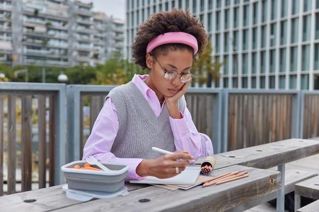 女の子はノートに絵を描くクレヨンを使用してメモ帳に集中したペンを保持します丸い眼鏡をかけ、都会の環境に対して外できれいな服のポーズをとる