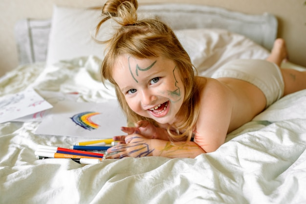 Girl draws a rainbow on white paper with felt-tip pens on the bed. children play in the morning at home. mischievous naughty baby, smeared hands, feet and face in paints, dirty.