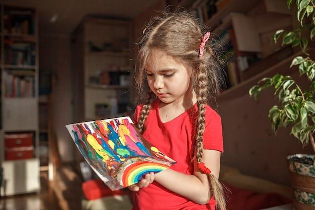 女の子は、アートのアイデアを溶かすためにブロードライヤーとワックススターを使用して、溶けたクレヨン鉛筆で虹を描きます