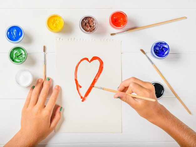 The girl draws a red outline of the heart on a white table. flat lay.