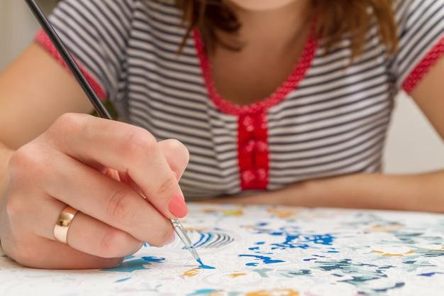 Девушка рисует кистью по номерам на холсте крупным планом
