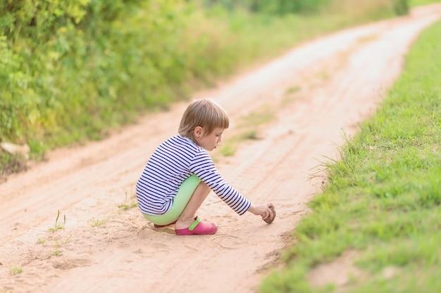 Девушка рисует камнем на песке, сидя на корточках на песчаной деревенской дороге. мягкий фокус, выборочный фокус