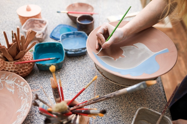 Girl draws with a brush on earthenware.