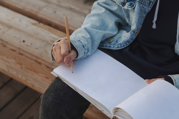 Girl draws with a pencil on a blank sketchbook page