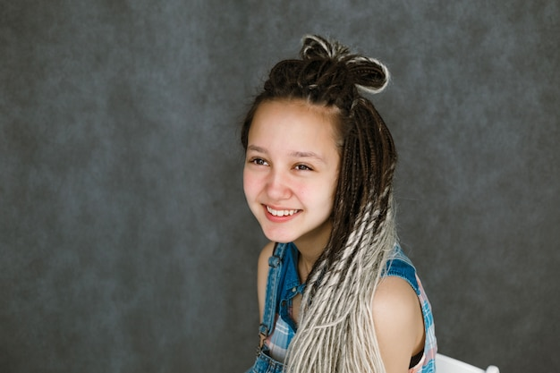 The girl in the dreadlocks is smiling.