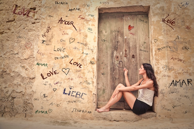 Girl dreaming of love at an old door in summer