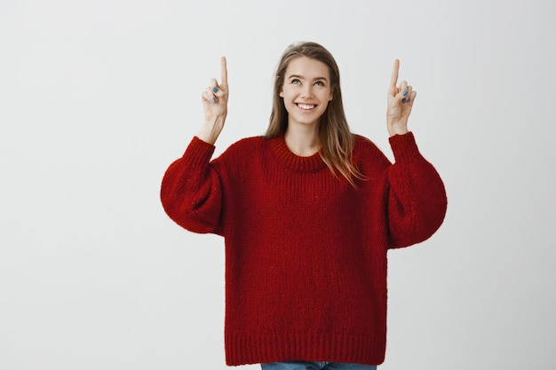 Girl dreams to live in skyscrapper. dreamy attractive feminine girlfriend in stylish loose sweater, raising index fingers and pointing upwards, smiling broadly, being interested and intrigued