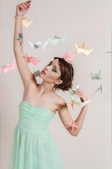Girl dreams paper of birds. origami cranes dragons