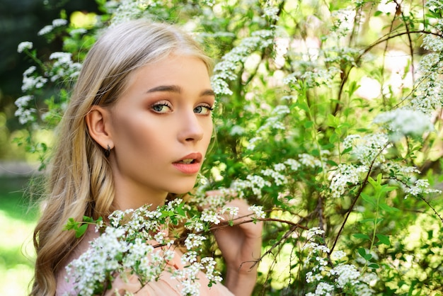 Girl on dreamy face, tender blonde near branches with white flowers. young woman walks in park on sunny spring day