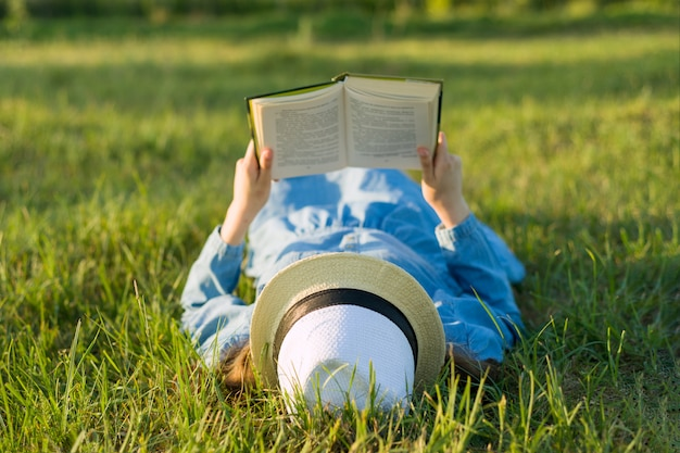 Girl in dress and hat lies on green grass reading book.