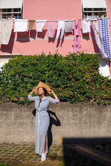 A girl in a dress and hat walks in the afternoon in an italian town in tuscany.
