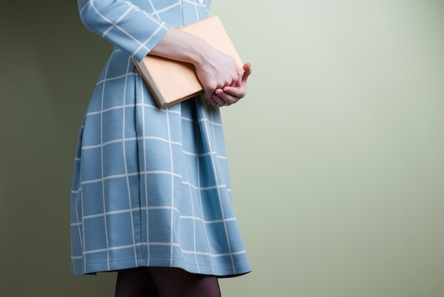 Girl in dress holding a book with her hands