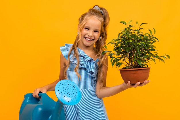 Girl in a dress holds a plant and a watering can on an orange wall