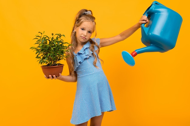 Girl in a dress holds a pot plant and a watering can on an orange wall