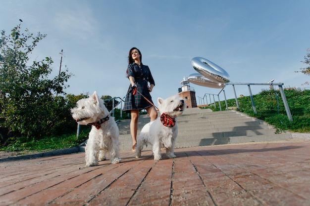 Girl in a dress next to the lighthouse on a walk with two white dogs