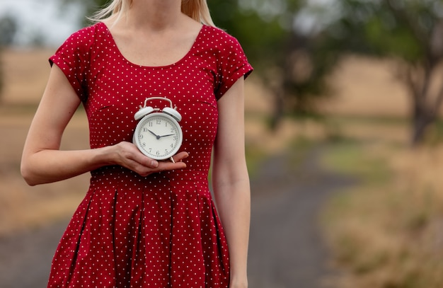 Girl in a dress in polka dot with alarm clock on rural road