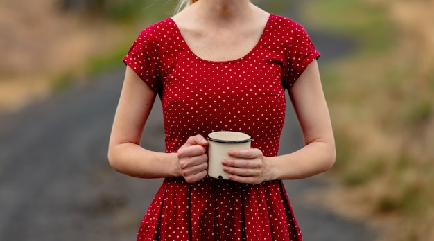 Girl in a dress in polka dot with cup on rural road