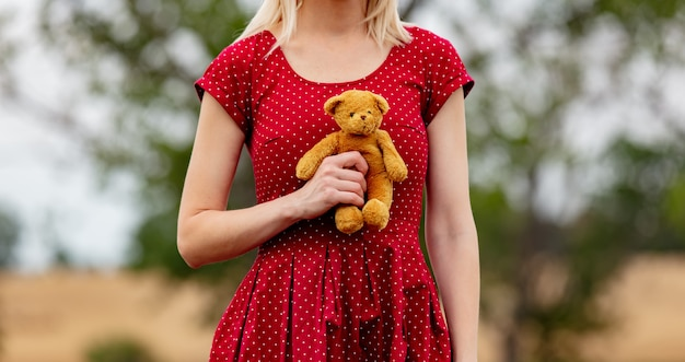 Girl in a dress in polka dot with teddy bear on rural road