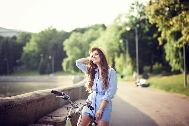 Girl in dress riding a bicycle through the city