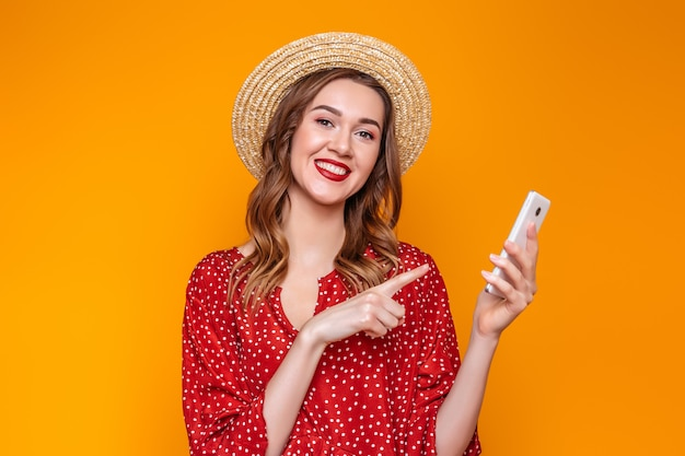 Girl in a dress, a straw hat holds a mobile phone and points a finger at him isolated over orange background