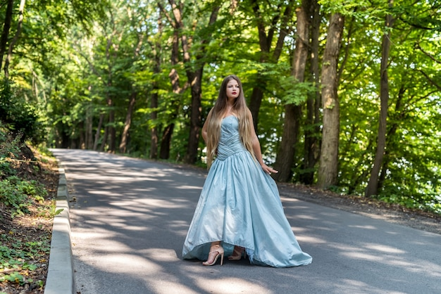 Girl in dress on the summer road between trees