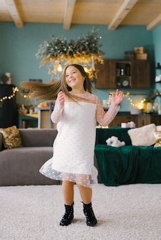 Girl in a dress whirling around the christmas tree