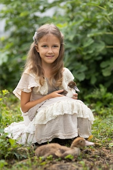 Girl in a dress with an apron grazes ducklings