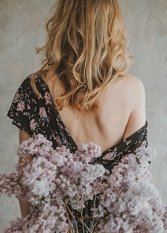 Girl in a dress with a back with a bare shoulder and a bouquet of lilacs